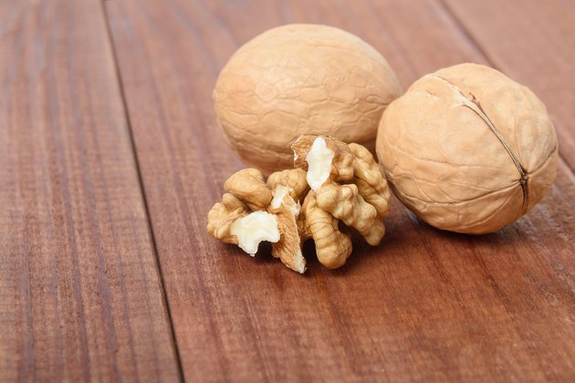 Ripe walnuts close-up on a brown wooden table