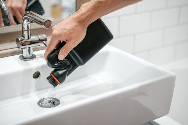 Removal of blockage in the sink, the hand of a man with a bottle of a special remedy with granules.
