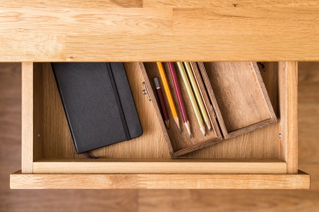 Notebook and pencils in open desk drawer top view