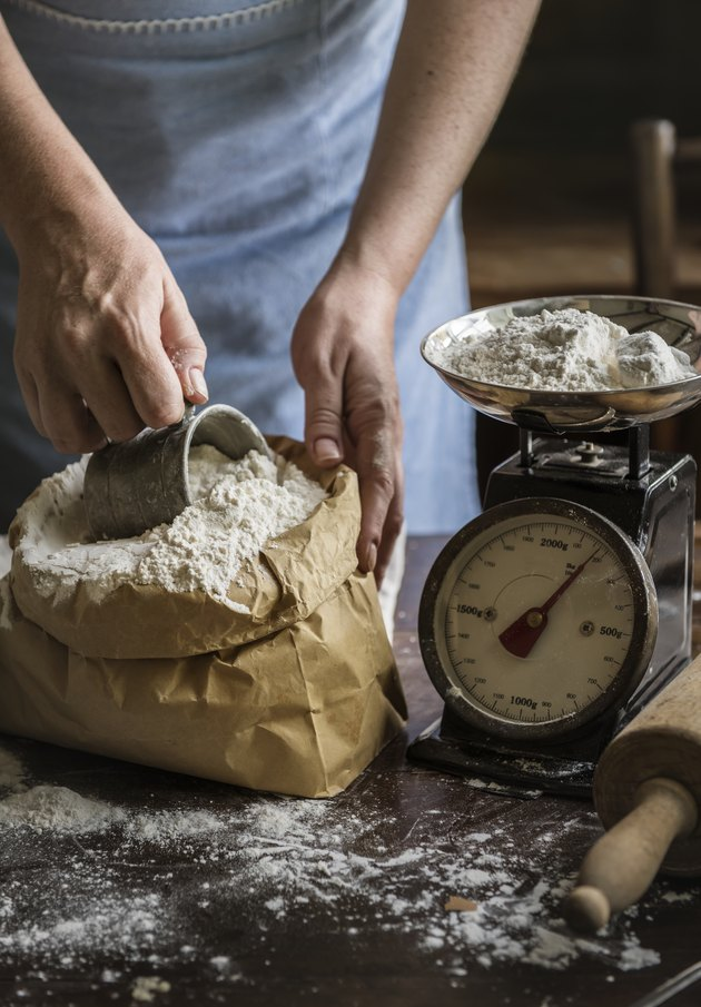 Baker weighing flour on a scale.
