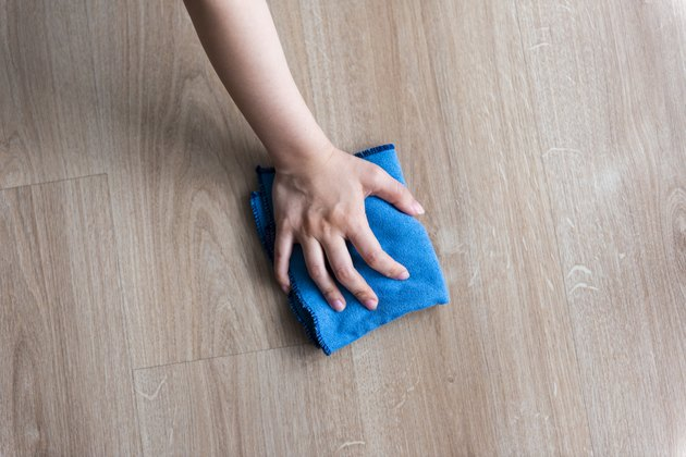 Woman cleaning wooden floor