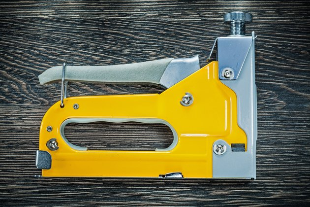 Building stapler gun on wooden board