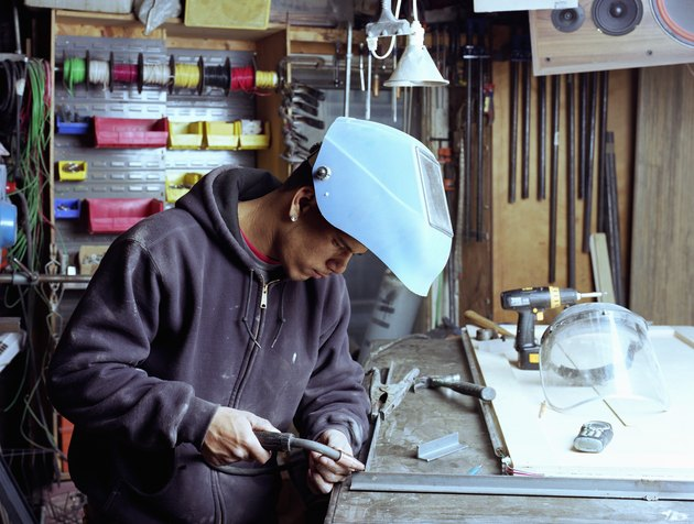 Young workman welding joint on metal frame