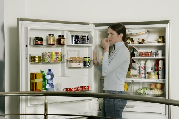 Young woman standing by refrigerator, side view