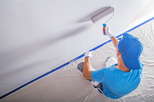 High Angle View Of Worker Painting On Wall At Home