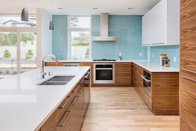beautiful modern kitchen in new contemporary style luxury home, with island, pendant lights, hardwood floors, and stainless steel appliances. Features blue tone tile that extends to the ceiling