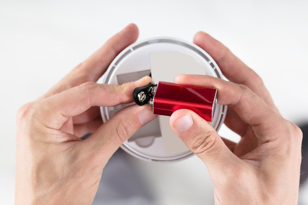 Person's Hand Inserting Battery In Smoke Detector