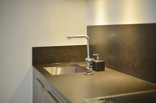 Luxury faucet on black sink with lighting in kitchen