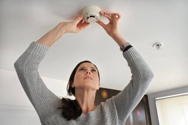 Woman checking smoke detector