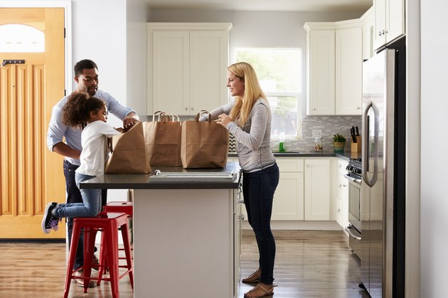 Girl and mixed race parents unpack shopping bags in kitchen