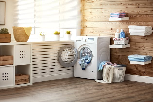 Interior of real laundry room with  washing machine at window at home