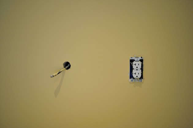 Coaxial cable hanging out of freshly painted wall next to an electric outlet 3 prong plug during renovation and construction