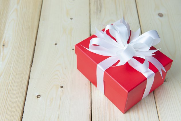 Red gift box seasoning crebration decoration on clean wooden background.