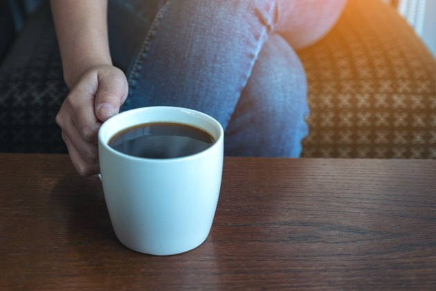Closeup image of a woman's hand holding a cup of hot coffee to drink while sitting in cafe