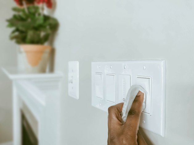 Woman Cleans Light Switches Using Disinfectant Wipe