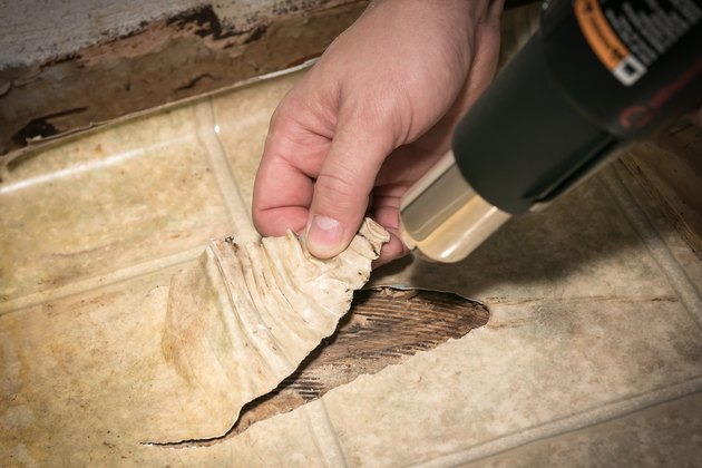 Preparing a ripped section of vinyl kitchen flooring for repair, with heat gun to soften and stretch vinyl over hole.