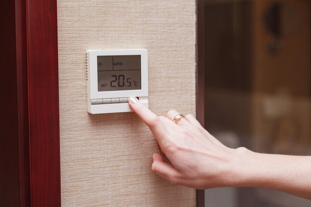 Woman switching a digital thermostat.