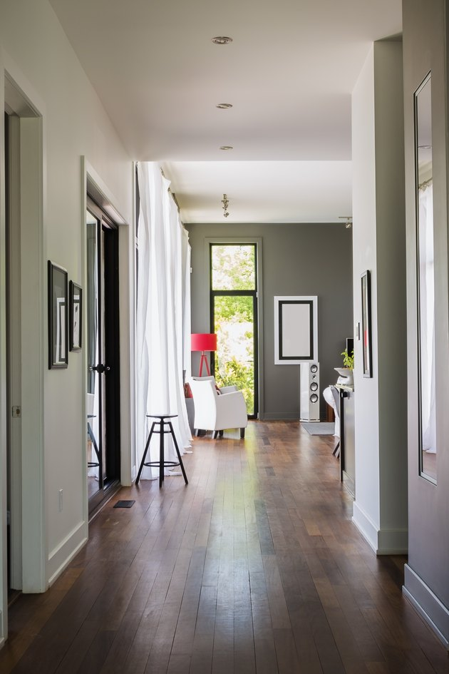 Hallway with qumaru wood floorboards.s leading to living room with white leather armchair, luxurious modern cube style house interior