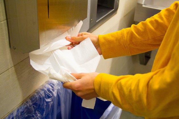 Hands Getting Paper Towel in Bathroom