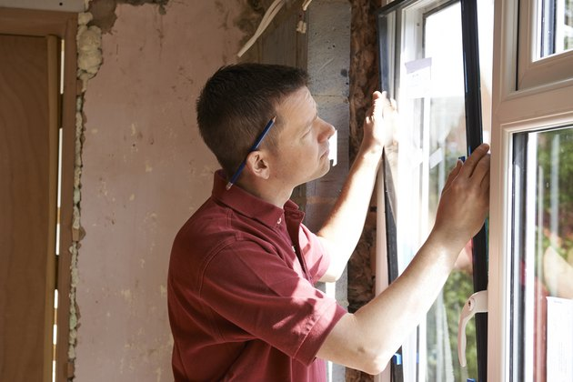 Construction worker installing new windows in house.