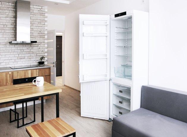 Scandinavian kitchen design with open fridge and sofa, oak furniture, horizontal