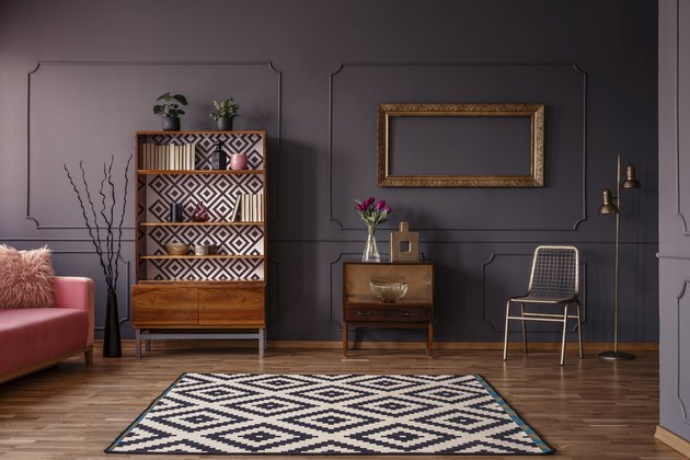 Vintage living room interior with a patterned rug, cupboard, golden frame on the wall, chair and wall molding