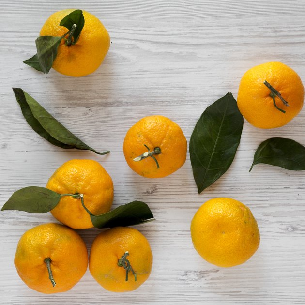Fresh ripe tangerines on a white wooden surface, top view. Flat lay, from above, overhead.