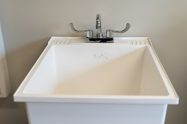 White plastic laundry sink, turned off, in a laundry room