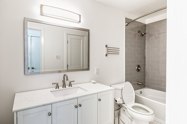 Freshly renovated bathroom with shower, toilet, mirror, faucet and sink