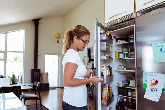Side view of woman using mobile phone while standing by open refrigerator at kitchen