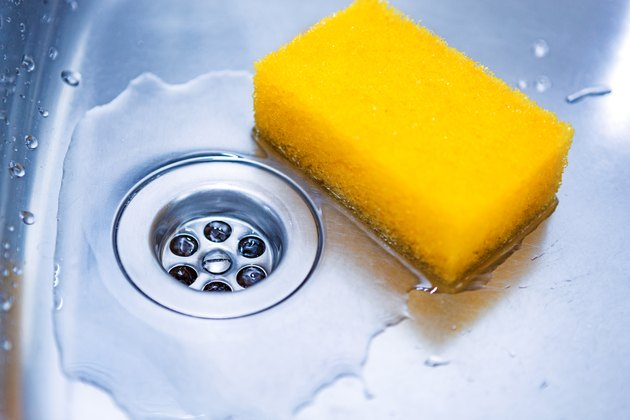 Yellow sponge in kitchen sink close up