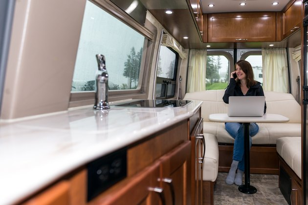 Young Woman Talking on phone and Using Laptop Inside Motorhome