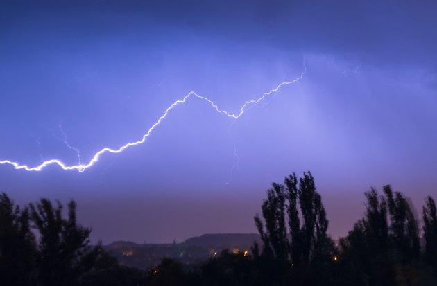 Night lightning storm over city in blue dramatic lighting