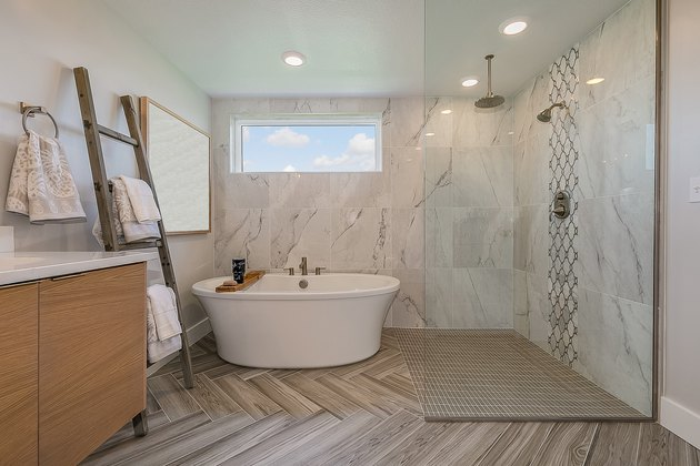Freestanding bathtub sits right next to open shower and beautiful chevron patterned flooring