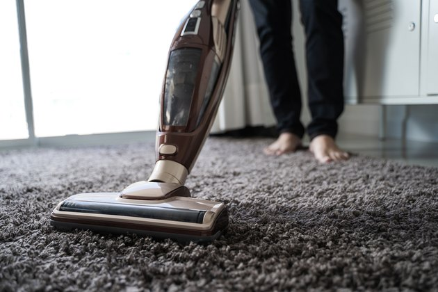 Low Section Of Man Cleaning Carpet With Vacuum Cleaner At Home