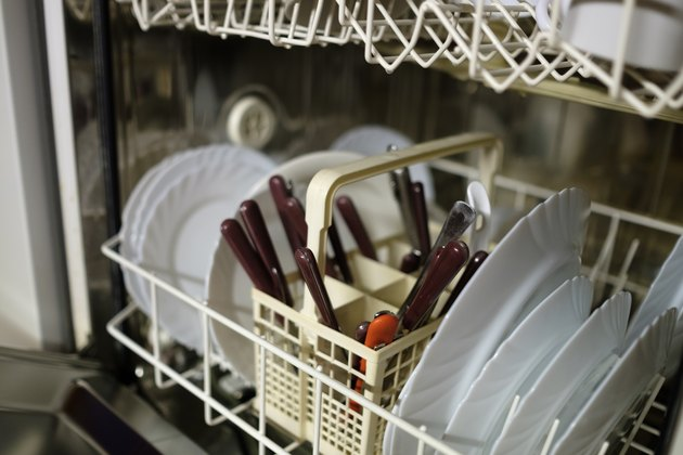 Dishwasher before cleaning process. Dirty plates ready to wash.