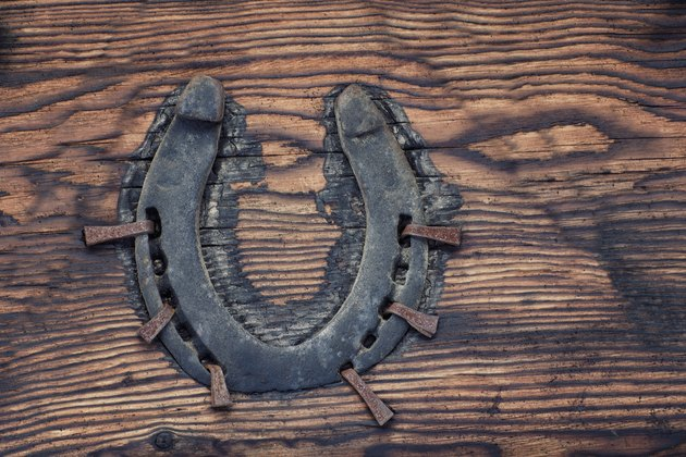 Old horseshoe nailed to a wooden board. Close up