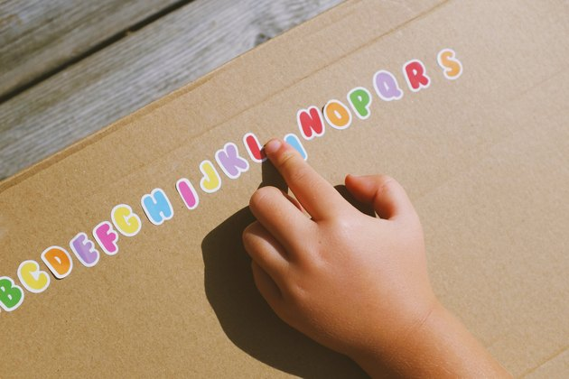 Child's hand and alphabet stickers
