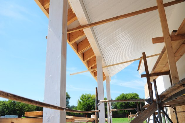 Building house patio roofing with wooden pillars and unfinished soffits and fascia boards installation.