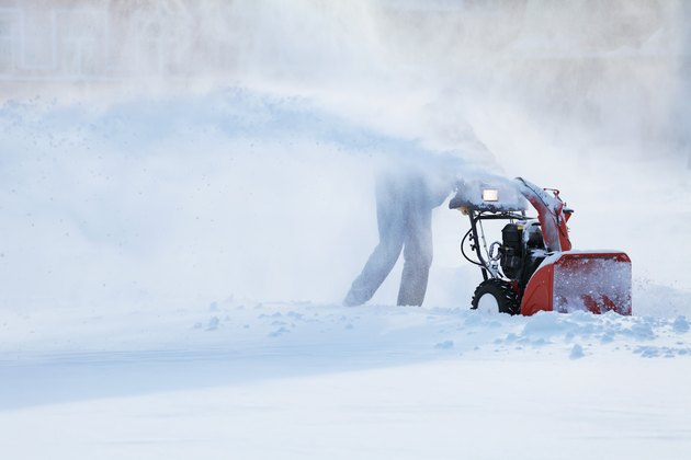 man with a snow blowing machine