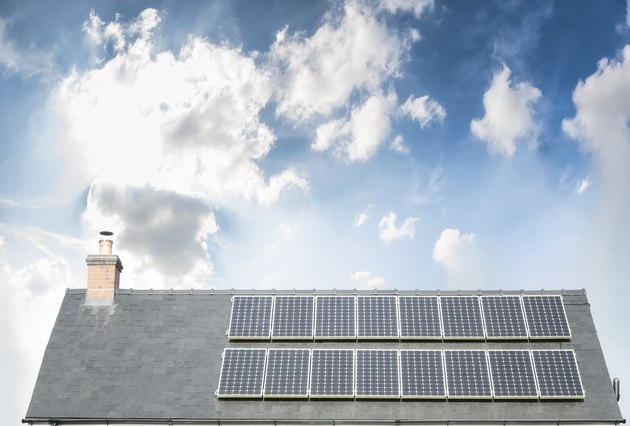 Solar Panels On The Roof Of A House Under A Bright Sky