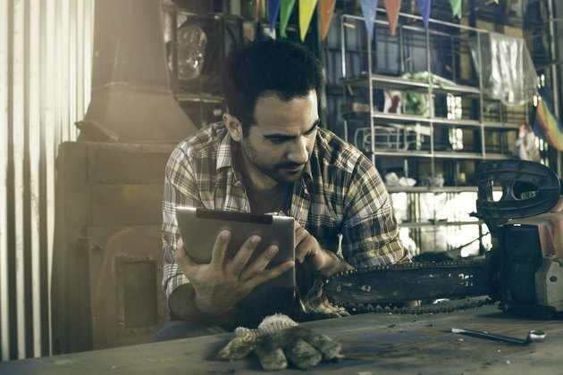 Man referencing chainsaw repair instructions on digital tablet