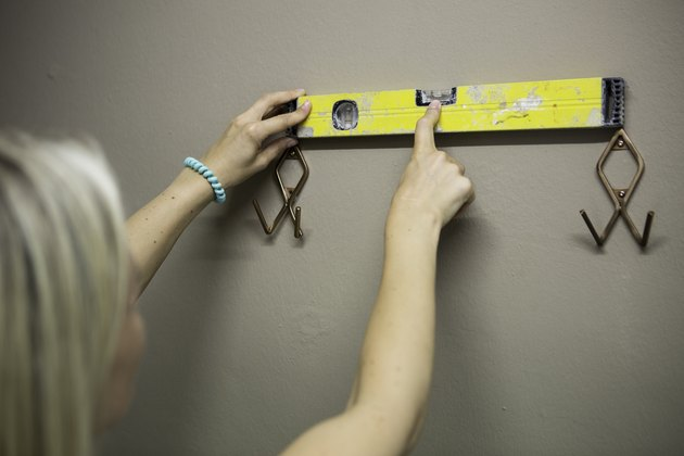Blonde woman measuring with water level to fix coat hooks