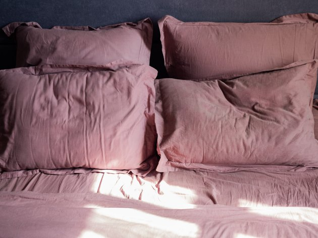 Four crumpled pillows and a sheet on the bed and the sun is shining on them
