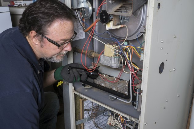 Technician Looking Over A Gas Furnace