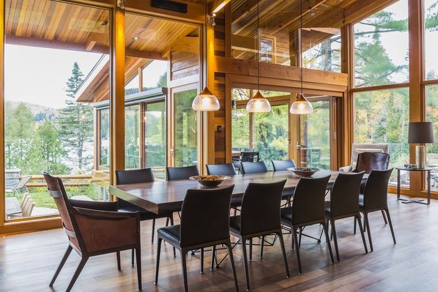 Wooden dining table with rawhide armchairs, black leather chairs and illuminated industrial style copper with  frosted glass pendant lighting fixtures in dining area of great room with Ipe wood floor inside luxurious stained cedar and timber wood home wi