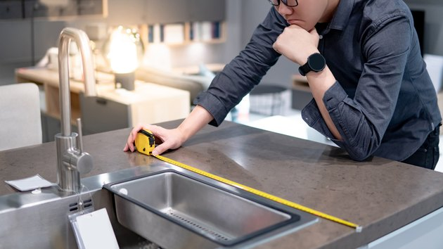 Asian man using tape measure on kitchen counter