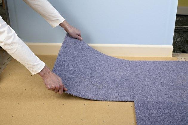 Man installing carpet tiles on top of hardboard floor