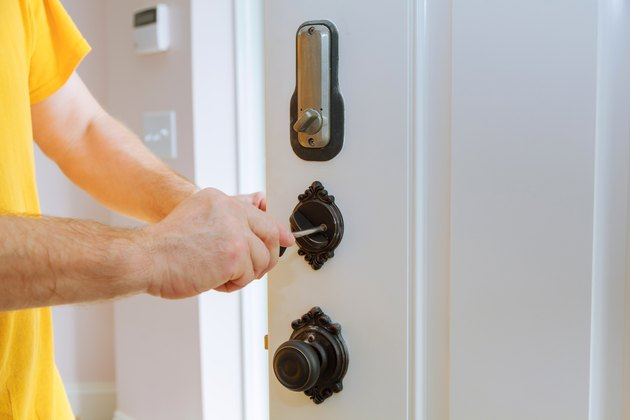 Closeup of a professional locksmith installing or repairing a new deadbolt lock