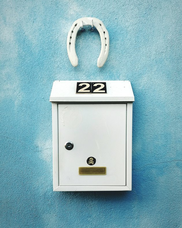 Close-Up Of Number On Mailbox Mounted Over Blue Wall With Horseshoe